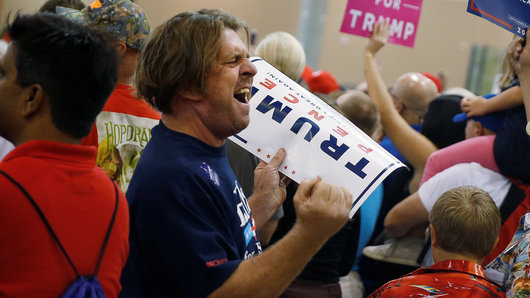 A man yells at the media as Republican presidential nominee Donald Trump speaks during a campaign event in Phoenix